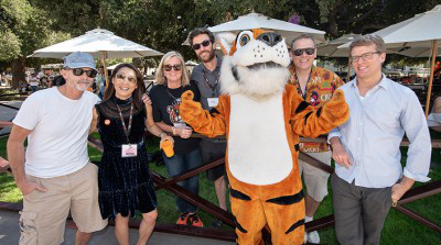 Oxy alumni pose with Oswald, Oxy's Tiger mascot