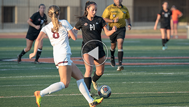 Student wearing black uniform kicks soccer ball while her opponent runs to meet her