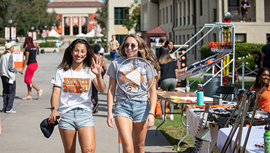 Two students wearing Oxy T shirts walk and wave, backed by Thorne Hall
