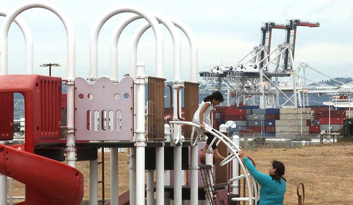 child at a playground near industrial activity